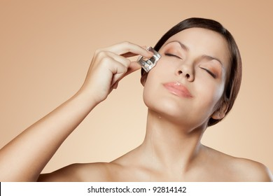 brunette woman holding ice cube on her face