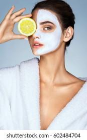 Femme brunette tenant une tranche de citron devant son visage. Photo de femme avec masque facial hydratant. Beauté