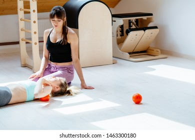 Brunette woman instructor helping client doing self-massage technique applying franklin ball for shoulder blade pain relief, working out lying on floor in pilates studio with equipment on background.