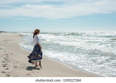 Brunette woman in a long dress walks along the seashore