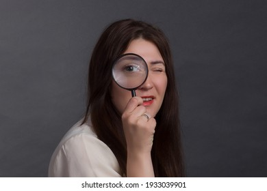 A brunette woman with long hair, wearing a beige blouse on a gray studio background. Looks at the camera through a magnifying glass
