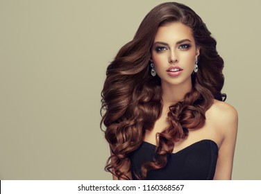 Brunette  woman  with long , healthy and   shiny curly hair .  Beautiful  model girl  with wavy hairstyle   .Care and beauty products