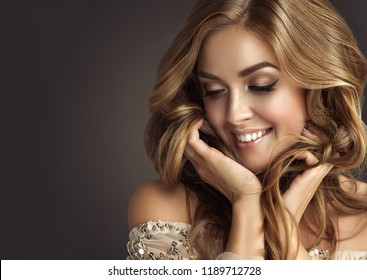 Brunette  woman with long  and   shiny wavy hair .  Beautiful  model with curly hairstyle .