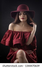 Brunette woman with long and shiny wavy hair in a red Hat. Beautiful model on dark background. Studio photosession