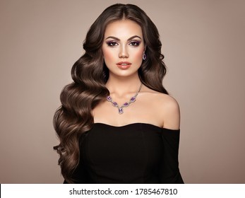 Brunette woman with long and volume shiny wavy hair . Beautiful model with curly hairstyle. Perfect make-up. Beauty style model
