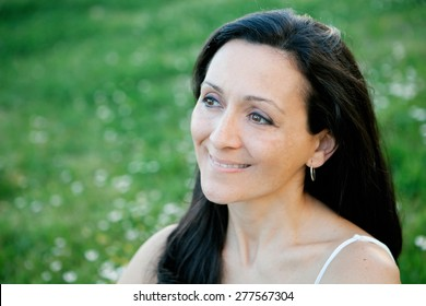 Brunette woman looking at side on a flowered meadow