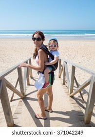 brunette woman mother carrying in backpack rucksack her two year blonde baby old with blue hat white sunglasses walking at a beach in Cadiz Spain