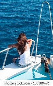 Brunette woman on bow of yacht with legs out