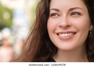 Brunette woman on a walk in european city. She smiles cheerfully. Urban on a background. Close up of her perfect smile with straight perfect teeth