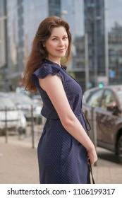Brunette woman on a walk in european city, wearing summer dress. She smiles cheerfully. Urban on a background