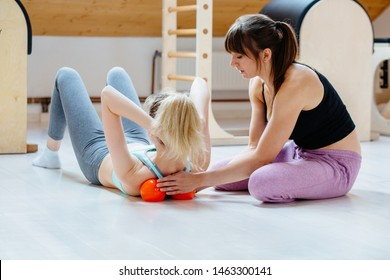 Brunette woman physiotherapist puts ball for reaxation shoulder blade of female client lying on back massaging patient technique applying orange ball. Treatment back pain concept. Practical use.