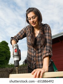 Brunette woman in pigtails drilling 2x4 boards with battery operated drill