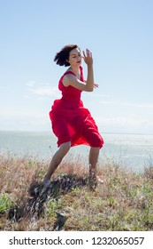 Brunette woman in a red dress is dancing in the nature
