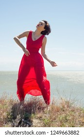 Brunette woman in red dress dancing in nature in summer