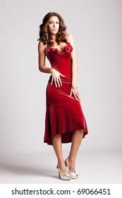 brunette woman in red elegant dress, full body shot, studio shot