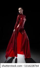Brunette woman in red latex slim suit posing on dark background