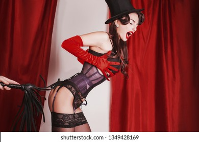 Brunette woman with red lips in long gloves. Girl with black hair and tan skin. Brunette woman in black fetish lingerie. Retro lady in vintage bdsm fetish clothes. Bdsm toy. Burlesque performance