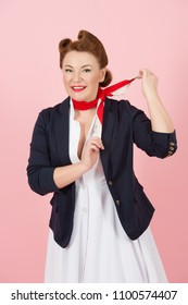 Brunette woman with red scarf on neck. Air uniform for girls on airplane. Happy girl with pin-up style and make-up in blue jacket take on the red scarf on pink background.