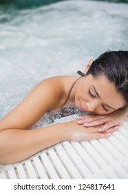 Brunette woman resting at edge of jacuzzi