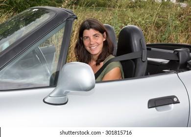 Brunette Woman Sat In A Convertible Sports Car