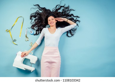 brunette woman seamstress tailor (dressmaker) lying on the floor with sewing machine and measuring tape on a blue background in studio view from top above.