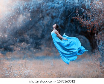 brunette woman in sexy dress flies to meet sun rays. Сoncept of happiness joy and freedom. Backdrop fabulous nature cold vibrant saturated color. fabric skirt wavy. Art levitation. Holiday Women's day