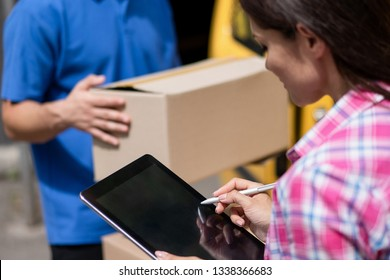 Brunette Woman Signs A Delivery Documents On The Tablet Using A Stylus. Profile Of Charming Female Customer Signing The Waybill On A Tablet. Blurred Image Of Courier In Blue Uniform Holding A