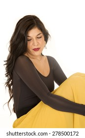 Brunette woman sitting looking down yellow skirt