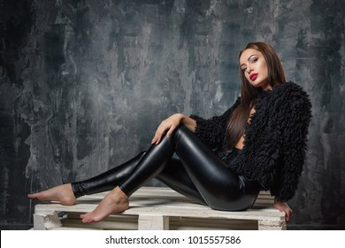 Brunette woman sitting on a barrel. Sexy female model in elegant black pants and short eco faux fur coat thinking and dreaming