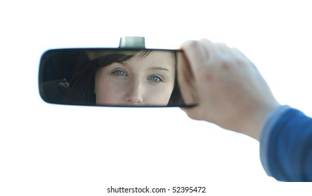 Brunette woman sitting on driver's seat and looking in the rear-view mirror