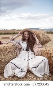 Brunette woman sitting on hay