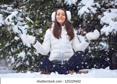 brunette woman sitting  in winter park under fur tree