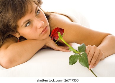 A brunette woman smelling a red rose.