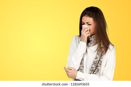 Brunette woman sneezing in a tissue