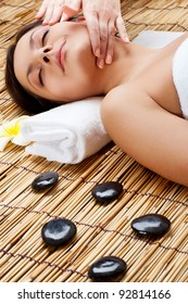 brunette woman in spa salon. Massage of neck and face