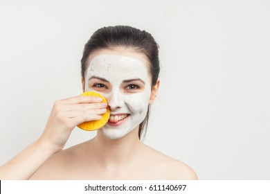 Brunette woman with sponge clear skin cream on face