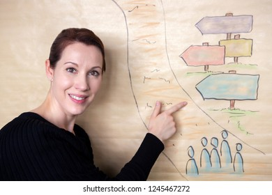 brunette woman standing at board and pointing at a drawing