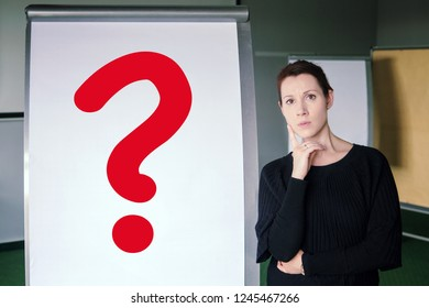 brunette woman standing next to flipchart with red question mark