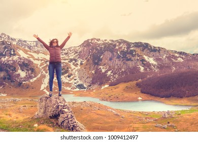 Brunette woman in sunglasses, jacket and jeans standing on a rock with his hands up against the background of mountains in autumn