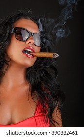 Brunette woman in sunglasses and in a red dress smoking a cigar.