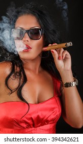 Brunette woman in sunglasses smoking a cigar.