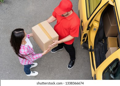 Brunette Woman Takes Her Delivery From A Courier In Red Uniform. Open Door Of A Yellow Delivery Van. Top View. Delivery Concept.