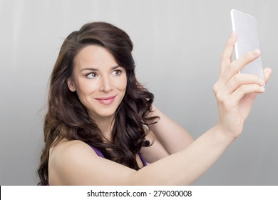 Brunette woman taking a photo of her self on a mobile device