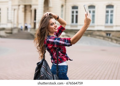 Brunette woman taking selfie with mobile phone walking along the street with backpack