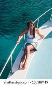 Brunette woman tanning shipboard of yacht in sunglasses