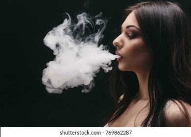 Brunette woman vaping electronic cigarette with smoke on black background closeup. Young woman smoking e-cigarette to quit tobacco. Vapor and alternative nicotine free smoking concept, copy space