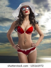 brunette woman with very sexy bikini, big sunglasses and summer white hat with cloudy sky background