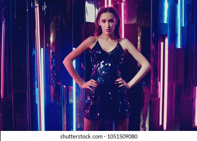 Brunette woman wearing elegant black sequin strap cami dress standing on dark interior with mirrors. Attractive caucasian female model posing against glowing neon lamps and mirrors on background