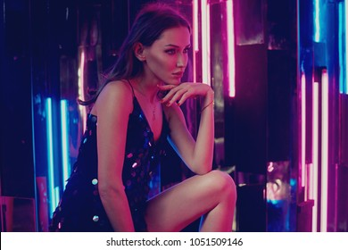 Brunette woman wearing elegant black sequin strap cami dress standing on large cube. Attractive caucasian female model posing against glowing neon lamps and mirrors on background