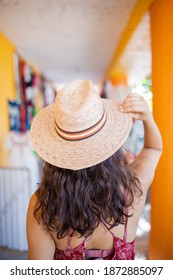 Brunette woman wearing red dress and straw hat standing next to hat rack. Young woman trying on different straw hats. Summer beauty and fashion